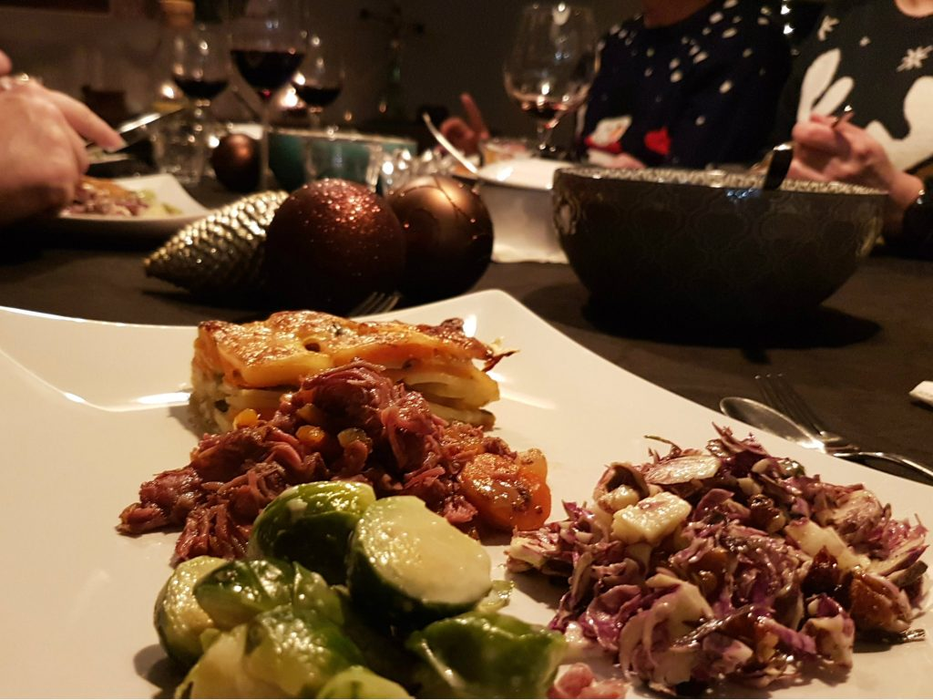 Stoofvlees van varkenswangen met gratin en spruitjes op kersttafel