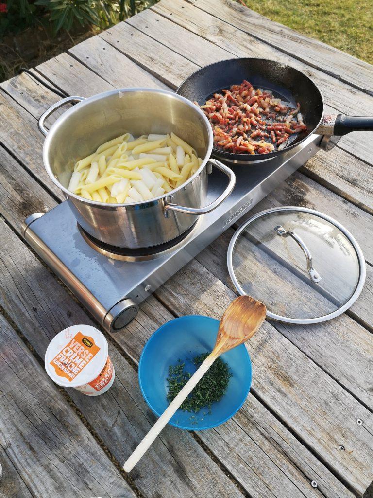 Pasta met asperges en spekjes op kookplaatje buiten