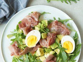 Lunchsalade op bord met rookvlees, avocado en ei